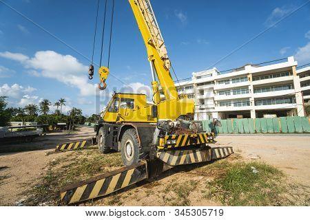 Yellow Automobile Crane With Risen Telescopic Boom Outdoors. Mobile Construction Crane On A Construc