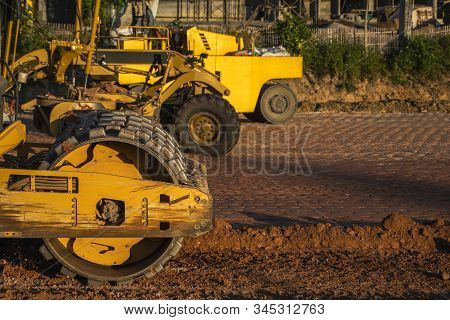 Soil Compactor With Vibratory Padfoot Drum. Heavy Duty Machinery Working On Highway Construction Sit
