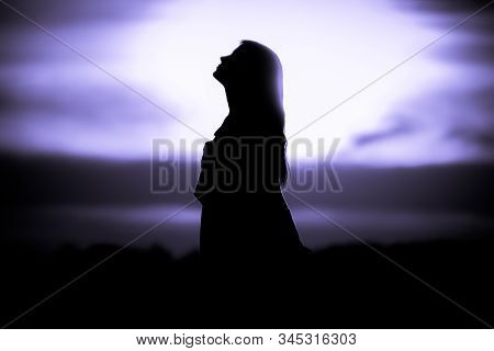 Youth Woman Soul At Purple Sun Meditation Dreaming Past Times. Silhouette In Front Of Sunset Or Sunr