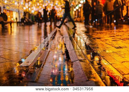 Rainy Night In A Big City, Reflections Of Lights On The Wet Road Surface. The View From The Street L