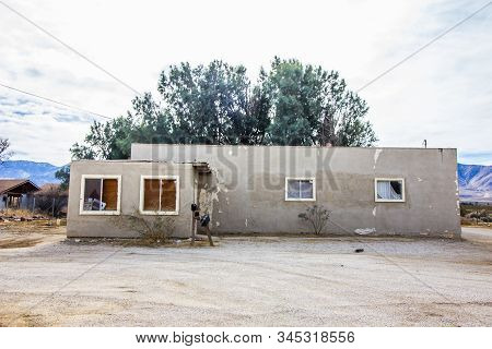 Abandoned Adobe Home With Peeling Paint And Boarded Up Windows