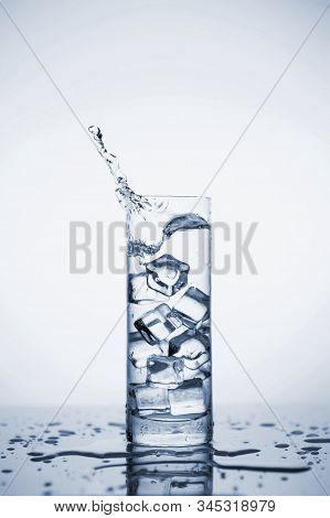 Clear Mineral Water Splashes In A Glass With Ice. Fluid In Motion. Copy Space. Close Up And Vertical