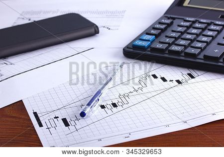 There Is A Calculator Pen Receipt And Financial Chart On The Table