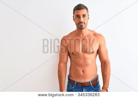 Young handsome shirtless man showing muscular body over isolated background Relaxed with serious expression on face. Simple and natural looking at the camera.