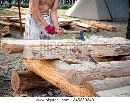 Carpenter Bare-chested In Medieval Cotton Clothes Working With Hardwood With An Ax. A Man Manually C