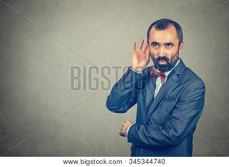 Man Eavesdropping Hand To Ear Trying To Listen Secretely To A Juicy Conversation. Mixed Race Bearded
