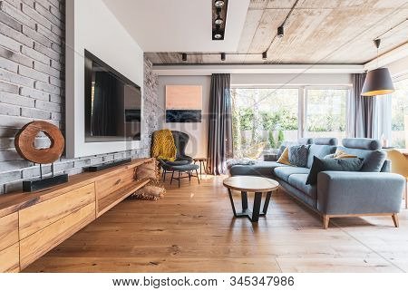 Elegant Living Room With Light Wooden Floor, Grey Couch And Wing Back Chair And Big Tv On The Wall
