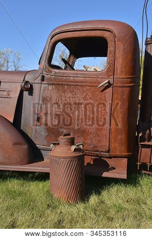A Rusty Old Milk Can Is In Front Of A Rust Covered Truck Creating A Scene Of Full Corrosion
