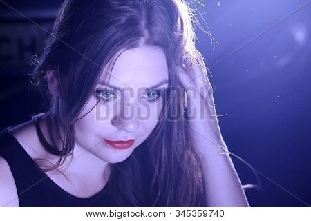 Young Beautiful Female With Green Eyes And Red Lipstick Looks Down, Smiling. Night Club Or Youngster