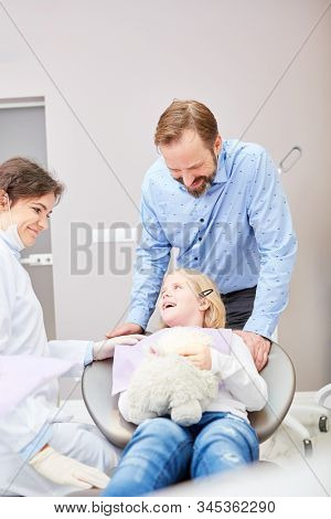 Dentist and dental assistant together with smiling child in the consultation room