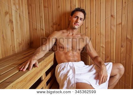 Attractive man is sitting to relax in the sauna of the hotel