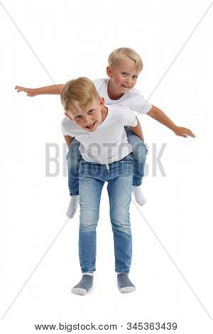 Friendly family. Older brother is carrying younger boy  on the back , isolated on a white background. Happy siblings. Two little brothers. Concept of people and family,