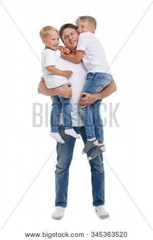 Friendly family. Young man holding two children stands isolated on a white background. Happy parent. Father with two son. Concept of people, parenting and family,