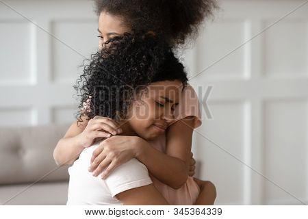 Close Up Sad Upset Black Woman Cuddling Daughter.