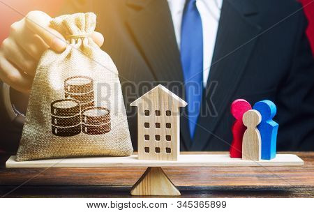 Man Puts A Money Bag And House On Scales With A Family. Mortgage, Debt Burden. Assistance With Housi