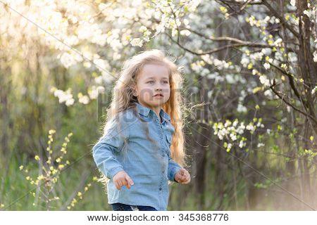 Little Blonde Girl Having Fun In The Spring Park.