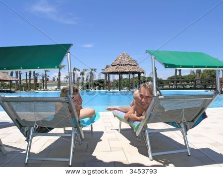 Happy Couple Enjoying Holiday At Swimming Pool