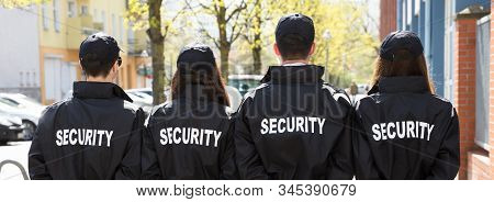 Security Guards With Hands Behind Back Standing In A Row Outside