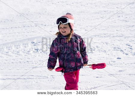 Joyful Adorable Girl Walking With Woolly Hat And Ski Goggles On Snowy Landscape