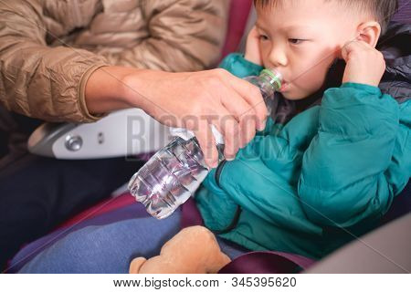 Asian 2 - 3 Years Old Toddler Boy Child Holding His Aching Ear And Drinking Water From Bottle During