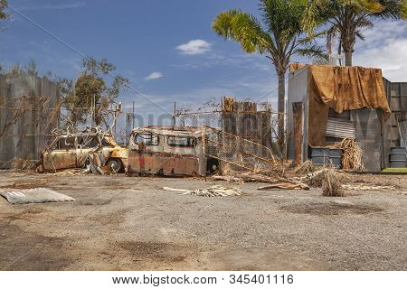 Rusty Car And Truck Next To A Metal Fence In A Junkyard