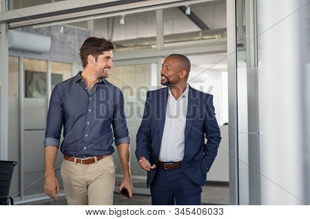 Multiethnic business colleagues walking in office while talking. Two successful business partners in modern office having conversation. Young businessman and mature boss discussing on new project.