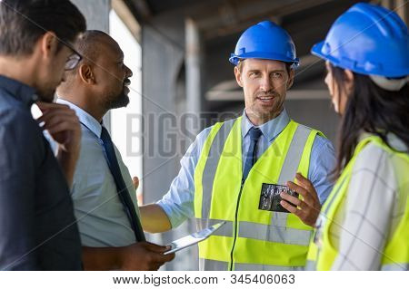 Happy mature engineer discussing the structure of the building with architects colleague at construction site. Engineers wearing safety hardhat having work conversation on the safety of the structure.