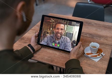 Smiling business partners talking through video call. Back view of man in coffe shop doing video chat calling a friend. Young man and his friend talking to each other through a videocall on tablet.
