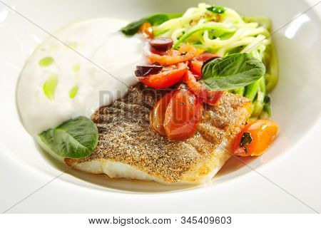 Cod fillet in cream sauce with vegetable spaghetti, fresh greens on white restaurant plate isolated. Macro shot of breaded white fish meat with cherry tomatoes, olives and spinach closeup