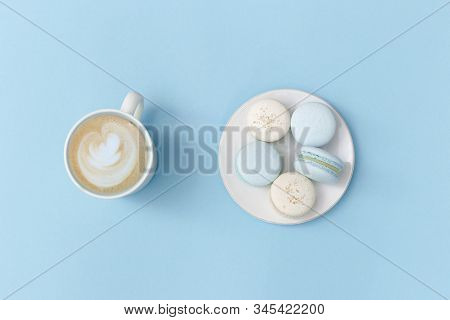 Coffe Cappuccino Art Foam In Big Mug And White Plate With Tasty Macarons On Bright Blue Background.