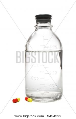 Botella médica con solución salina y pastillas al lado de él