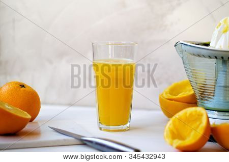 On A Wooden Table, One Whole Orange, One Cut In Half, Peel Of An Orange. On The Table Lies A Stone B