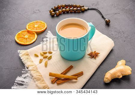 Traditional Indian Masala Tea Chai With Milk And On Napkin On Dark Stone Background With Ingredients