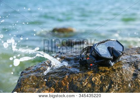 Wet Diving Mask On The Stone In The Sea. Diving Mask On A Rock Against The Background Of Ocean Waves