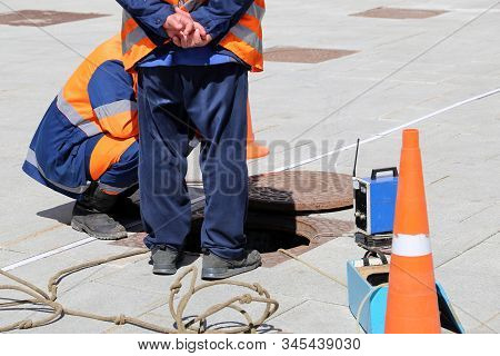 Workers Over The Open Sewer Hatch On A Street. Concept Of Repair Of Sewage, Underground Utilities, W