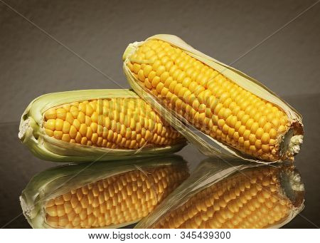 Still Life With Two Yellow Ripe Corn On Cob Against Low Key Background With Amazing Reflections. Sel
