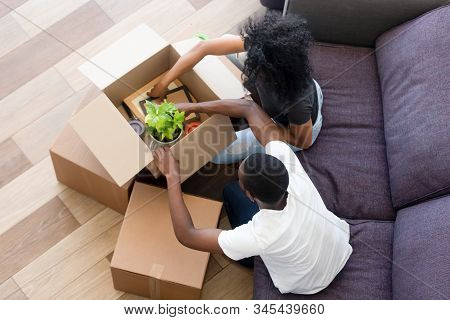 Top View Of Black Couple Unpack Boxes Settling In Home
