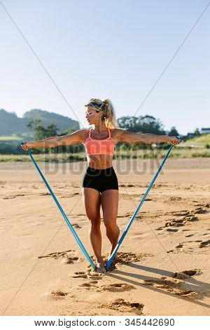 Fit Woman Training Shoulders With Resistance Band. Fitness Summer Morning Workout At The Beach. Late