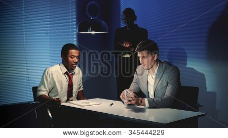 Accused Young Man Crumpling A Document With Accusation In Interrogation Room After Black Detective G