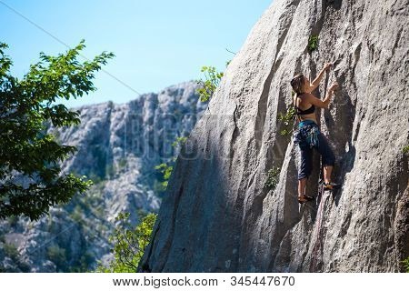 Climber Overcomes Challenging Climbing Route. A Girl Climbs A Rock. Woman Engaged In Extreme Sport.