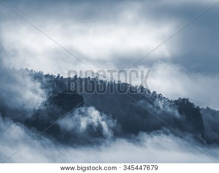 Dark Misty Weather In  Layer Of Tree And Mountain Hills Create Contours In Mist. Colorless Landscape