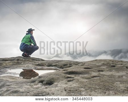 Lonely Man Sitting On Cliff Enjoy The View Over Deep Valley Full Of Morning Mist Above Forest Park.