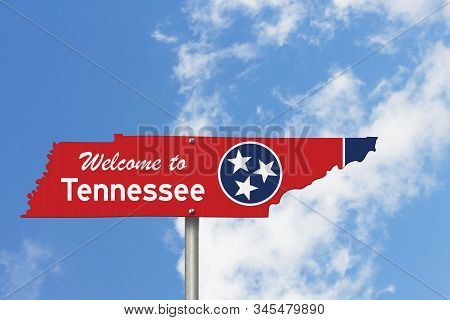 Welcome To The State Of Tennessee Road Sign In The Shape Of The State Map With The Flag With Sky Bac