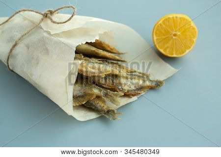 Fried Capelin With Lemon On Baking Paper On A Gray Background. Close-up