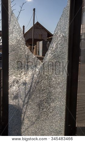 Broken Glass Bus Stop On The Highway. Vandals Smashed The Window. Small Fragments And Cracks Of Temp
