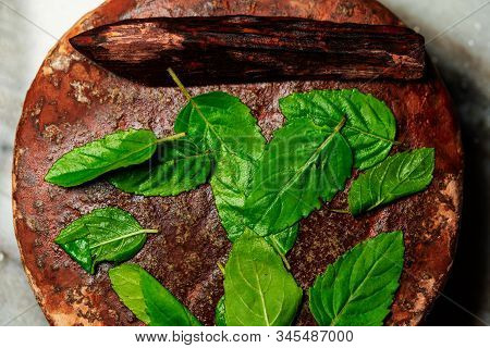 Background Image Of Sandalwood Stick Or Chandan And Grinding Stone With Holy Basil Leaves For Indian