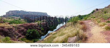 Panoramic View Of Mehrangarh Fort From Rao Jodha Desert Rock Park, Jodhpur, India. A Lake In Foregro