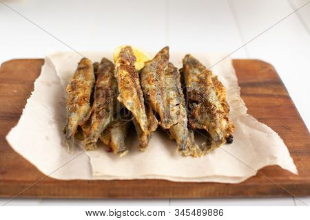Fried Capelin With Lemon On Baking Paper On A White Background. Close-up