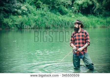Man With Fishing Rods On River Berth. A Fisherman With Fishing Rod On The River. Man Fishing And Rel