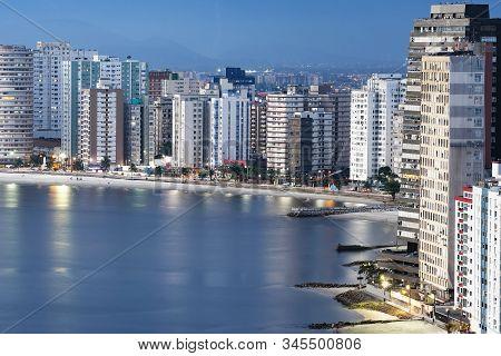 Urbanized Coast, Tall Buildings Near To The Beach Of A Coastal City At Dusk, When City Lights Begin